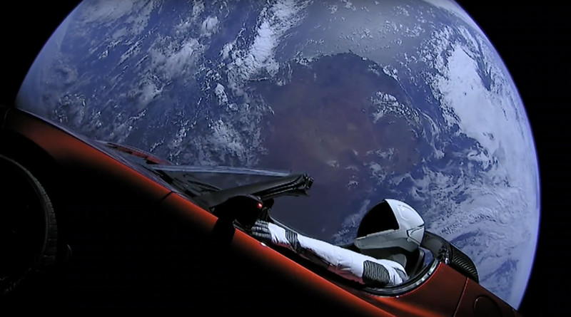Vista del coche Telsa en el espacio con la Tierra de fondo.