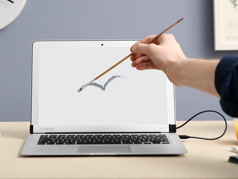 Ejemplo de que con la AirBar se puede utilizar un pincel con el portátil.