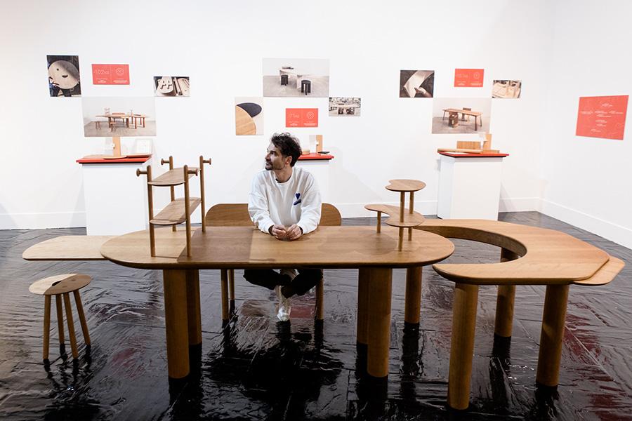 Jaime Hayon sentado en la mesa que ha diseñado