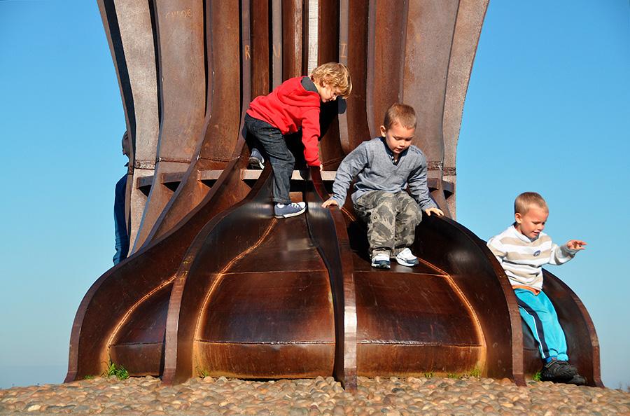 Escultura gigante Angel of the North, obra del escultor inglés Antony Gormley, detalle de la base con niños jugando en ella